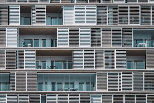Geometrische vooraanzicht van de luiken en balkons van een stedelijk gebouw gerangschikt in doorlopende rijen Premium Foto