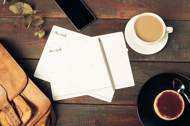 Geopend ambachtelijke papier envelop, herfstbladeren en koffie op houten tafel Gratis Foto