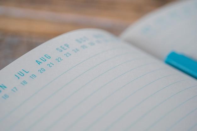 Geopend blauw leerboek met datummarkeringen bovenop op een houten oppervlak Gratis Foto