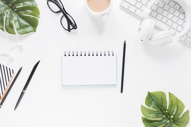 Geopend notitieboekje dichtbij kantoorbehoeften en elektronische apparaten Gratis Foto
