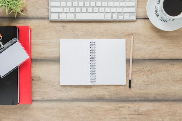 Geopend notitieboekje dichtbij kantoorbehoeftentoetsenbord en koffiekop Gratis Foto