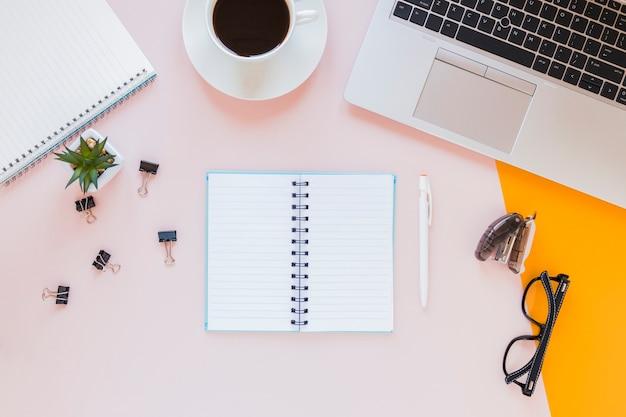 Geopend notitieboekje dichtbij koffiekop en glazen op roze bureau met kantoorbehoeften Gratis Foto