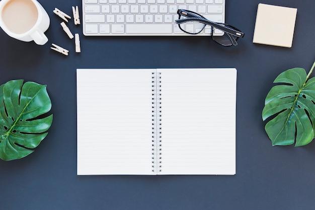 Geopend notitieboekje dichtbij toetsenbord en koffiekop op bureau met bladeren en glazen Gratis Foto