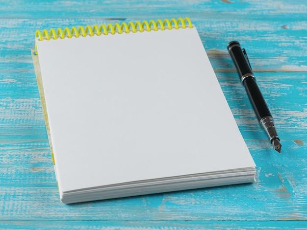 Geopend notitieboekje met een vulpen op een blauwe houten lijst Premium Foto