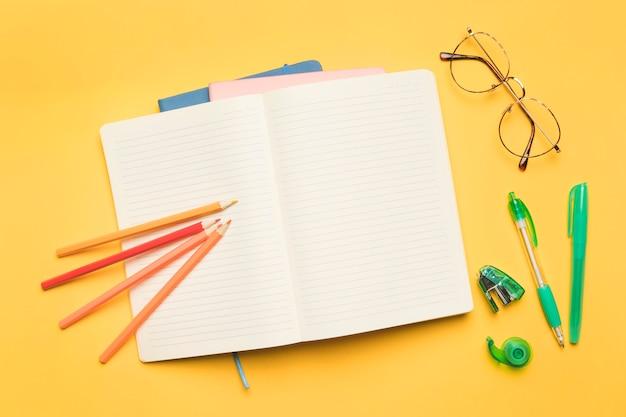 Geopend voorbeeldenboek dichtbij schoolbenodigdheden en glazen Gratis Foto