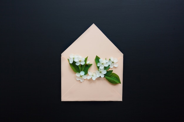 Geopende envelop met lente bloemen regelingen op zwarte achtergrond Premium Foto