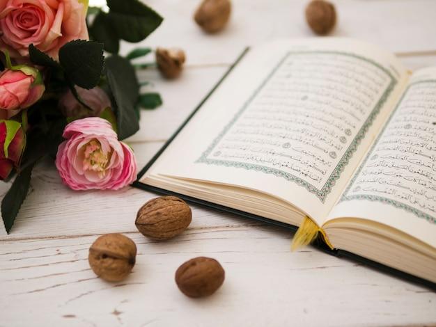 Geopende koran naast roze rozen Gratis Foto