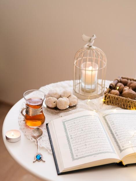 Geopende koran op tafel omringd door gebak en thee Gratis Foto