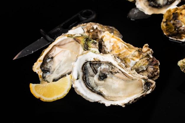 Geopende oesters, ijs en citroen op een zwarte ondergrond Gratis Foto