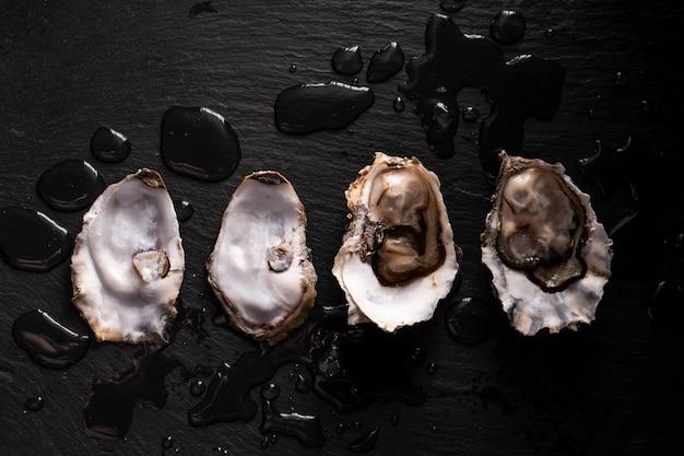 Geopende verse oesters op een donkere achtergrond en waterdruppels. rostik stijl. Premium Foto