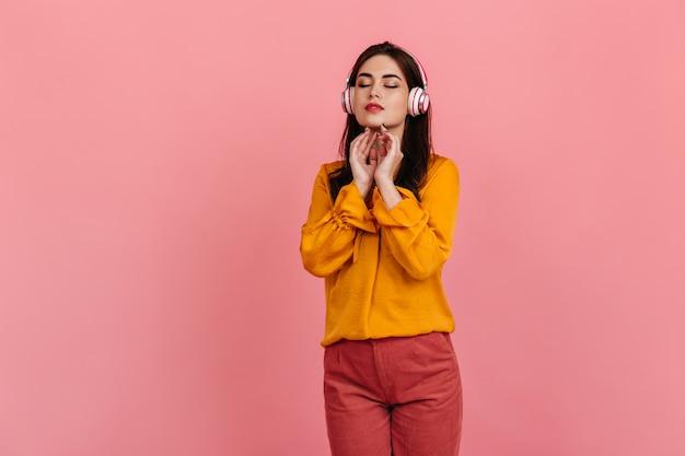 Gepacificeerde donkerharige dame in geel overhemd en lichte broek geniet van klassieke muziek in koptelefoon op roze muur. Gratis Foto