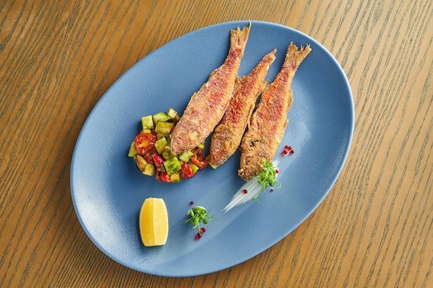 Gepaneerde gebakken zeevis (mul) met een bijgerecht van salade met avocado en tomaten op een blauw bord op een houten muur. close-up, selectieve aandacht Premium Foto