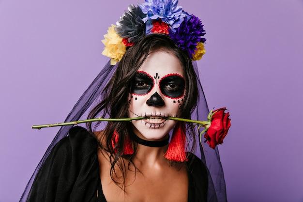 Gepassioneerde mexicaanse vrouw met geverfd gezicht met rode roos in haar tanden. close-upfoto van krullende brunette met kleurrijke bloemen in haar haar. Gratis Foto