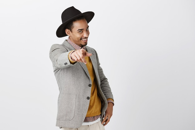 Gepassioneerde zelfverzekerde donkere man die voor jou kiest. portret van charmante afro-amerikaan in modieuze hoed en jas, hand trekken en met sensuele flirterige glimlach wijzen over grijze muur Gratis Foto