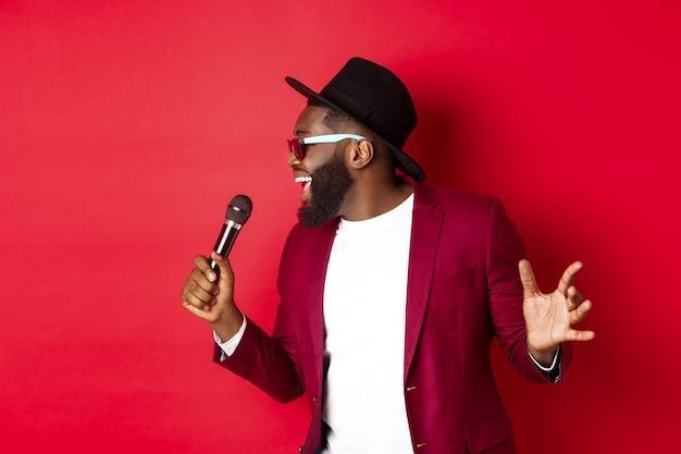 Gepassioneerde zwarte mannelijke zanger die tegen rood presteert Gratis Foto