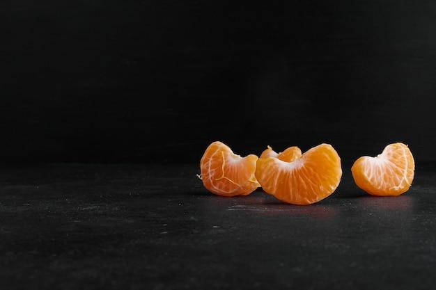 Gepelde en gesneden mandarijn op zwarte achtergrond, profielweergave. Gratis Foto