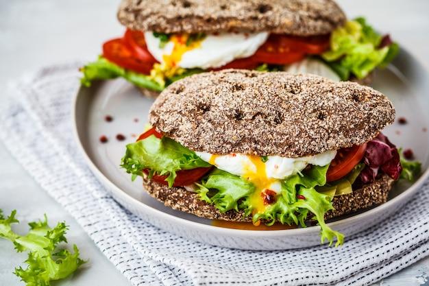 Gepocheerde ei sandwich met roggebroodje en tomaat op grijze plaat. Premium Foto
