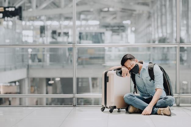 Geprobeerd aziatische man met gezichtsmasker rusten of slapen op de vloer van de luchthaventerminal Premium Foto