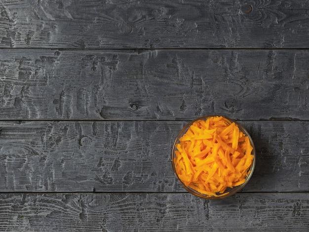 Geraspte verse wortelen in een glazen kom op een donkere rustieke tafel Premium Foto