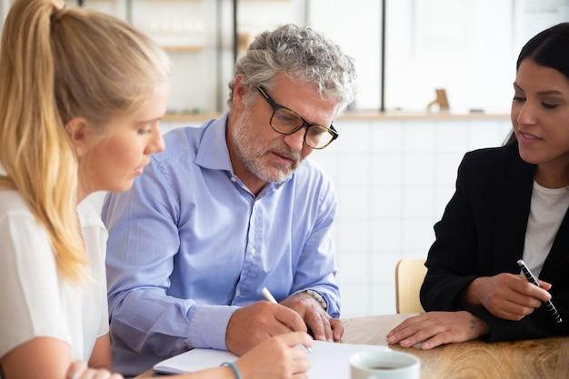 Gerichte jonge en volwassen klanten die een agent ontmoeten en een verzekeringsovereenkomst ondertekenen Gratis Foto