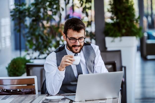 Gerichte kaukasische knappe bebaarde zakenman in pak en met bril kopje koffie te houden en laptop gebruikt. cafe buitenkant. Premium Foto