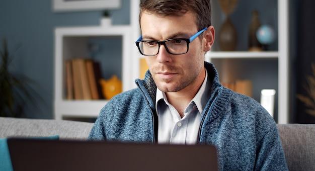 Gerichte man in brillen en casual kleding met behulp van laptop kijken scherm zittend op de bank in appartement Premium Foto