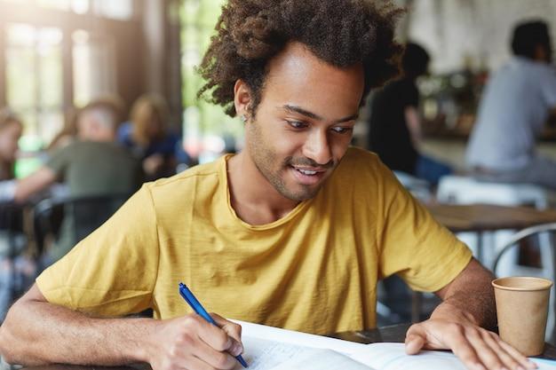 Gerichte student man met donker borstelig haar en varkenshaar dragen casual t-shirt schrijven iets in zijn notitieblok zittend in college kantine koffie drinken. knappe stijlvolle man schets schrijven Gratis Foto