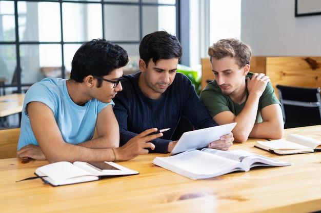 Gerichte studenten met behulp van tablet en het bespreken van informatie Gratis Foto
