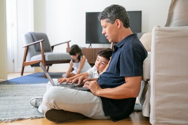Gerichte vader en zoontje zittend op de vloer in appartement, met behulp van laptop, werken of kijken naar inhoud. Gratis Foto