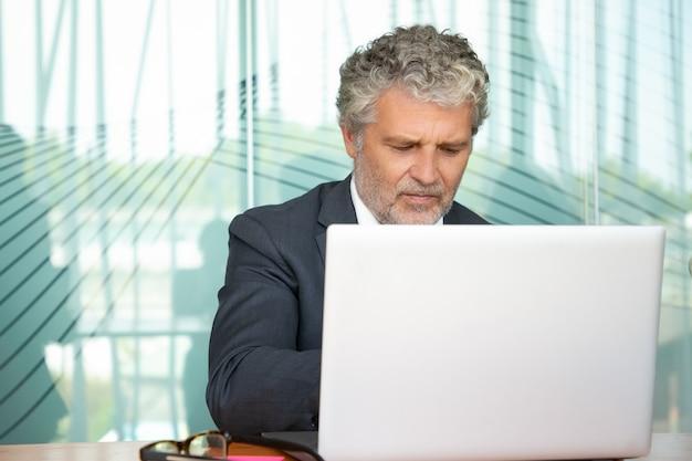 Gerichte volwassen executive werken op de computer in kantoor, met behulp van witte laptop aan tafel. m. Gratis Foto
