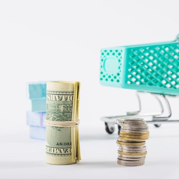 Gerolde dollars en muntstukkenstapel op witte lijst Gratis Foto