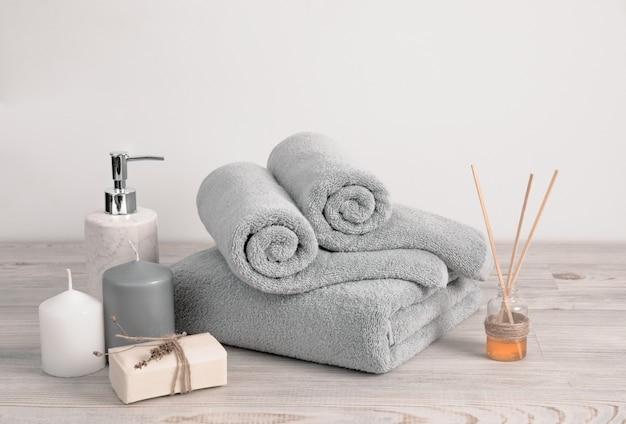 Gerolde en gevouwen grijze badstofhanddoeken met zeep en kaarsen tegen witte muur Premium Foto
