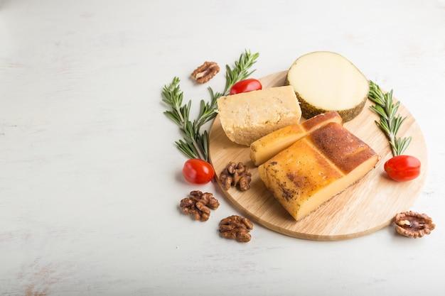 Gerookte kaas en diverse soorten kaas met rozemarijn en tomaten Premium Foto