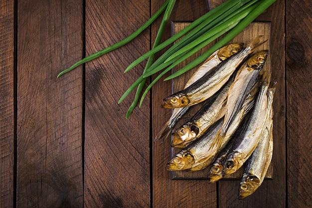 Gerookte sprot en groene ui op een snijplank. gerookte vis. bovenaanzicht Gratis Foto