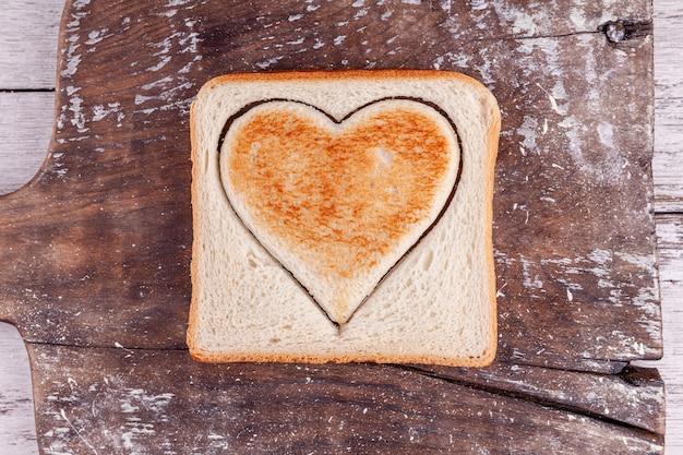 Geroosterd brood met gesneden hart op vintage bord, happy valentine's day Premium Foto
