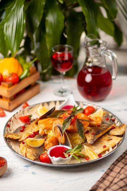 Geroosterde gegrilde vis en zeevruchten geserveerd met kruiden, citroen en dip rode tomatensaus. Gratis Foto