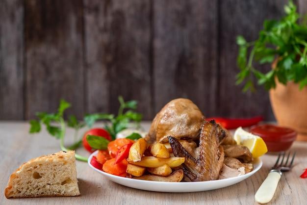 Geroosterde kip, aardappelen en groenten in plaat op hout. zijaanzicht. Premium Foto