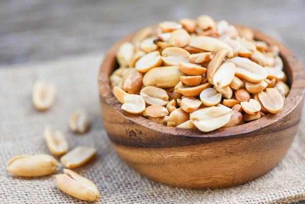 Geroosterde pinda's op een houten kom en zak - gezouten pinda's als voedsel of snack Premium Foto