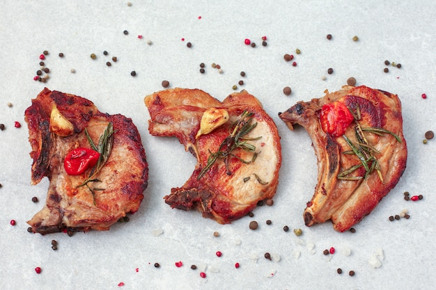 Geroosterde varkenslende steaks met kruiden en specerijen op lichte muur Premium Foto