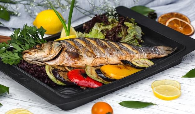 Geroosterde vis gegarneerd met plakjes citroen geserveerd met groenten Gratis Foto