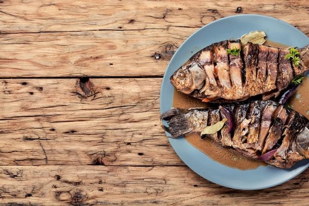 Geroosterde vis op houten achtergrond Premium Foto