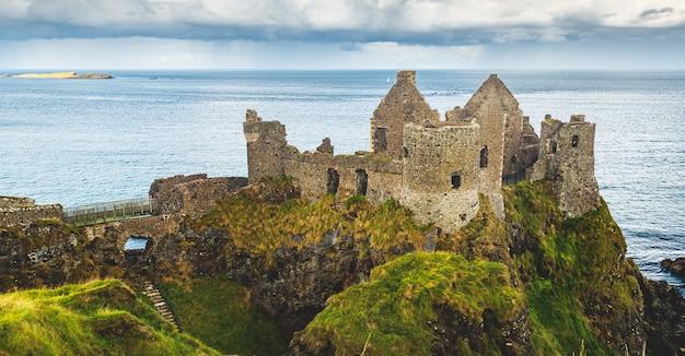 Geruïneerd oud kasteel bij kust noordelijk ierland Premium Foto