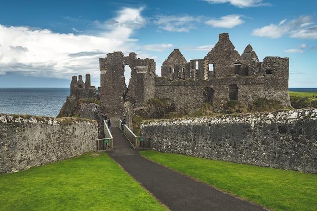 Geruïneerd oud kasteel bij kustlijn noordelijk ierland Premium Foto