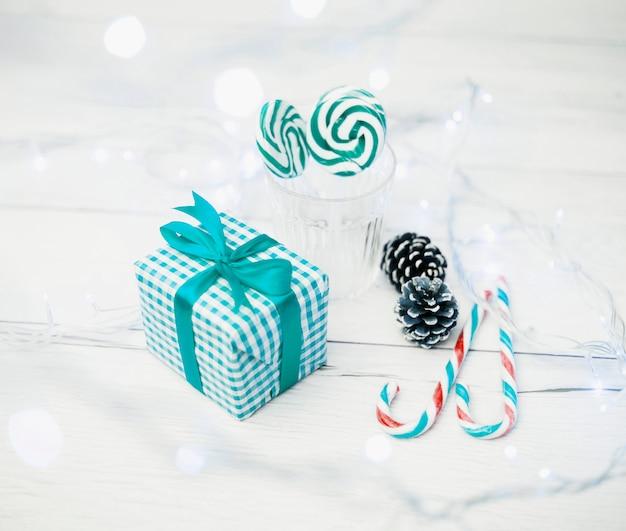 Geschenkdoos in de buurt van glas met lolly's, snoepriet en lichtjes Gratis Foto