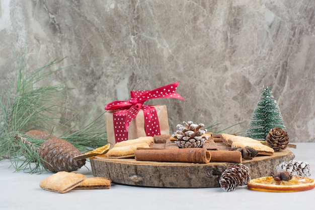 Geschenkdoos met boog en dennenappels op houten plaat. hoge kwaliteit foto Gratis Foto