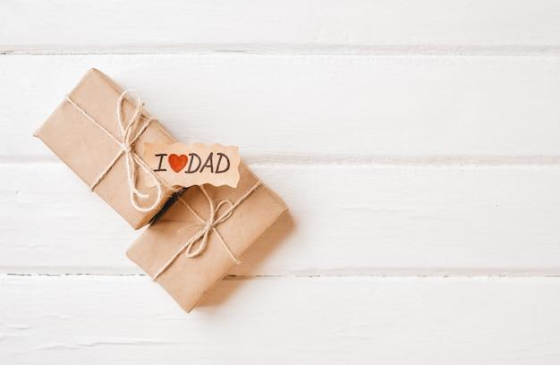 Geschenkdoos met een tag op witte houten ruimte. vaderdag of verjaardag concept. Premium Foto