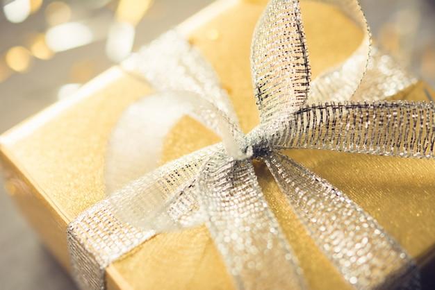 Geschenkdoos met glanzende glinsterende zilveren strik en goud inpakpapier Premium Foto