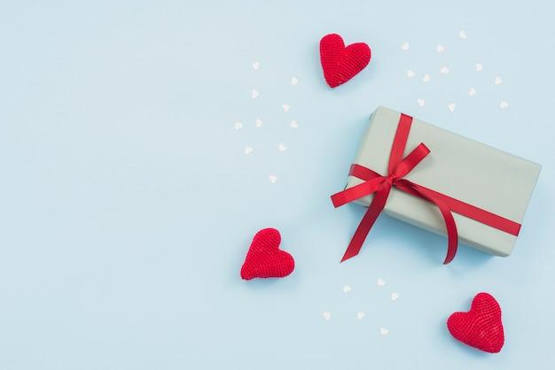 Geschenkdoos met rode speelgoed harten op tafel Gratis Foto