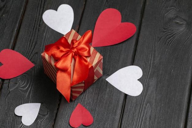 Geschenkdoos met rode strik lint en papier harten voor valentijnsdag Premium Foto