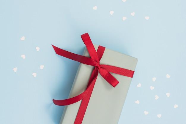 Geschenkdoos met rood lint op tafel Gratis Foto